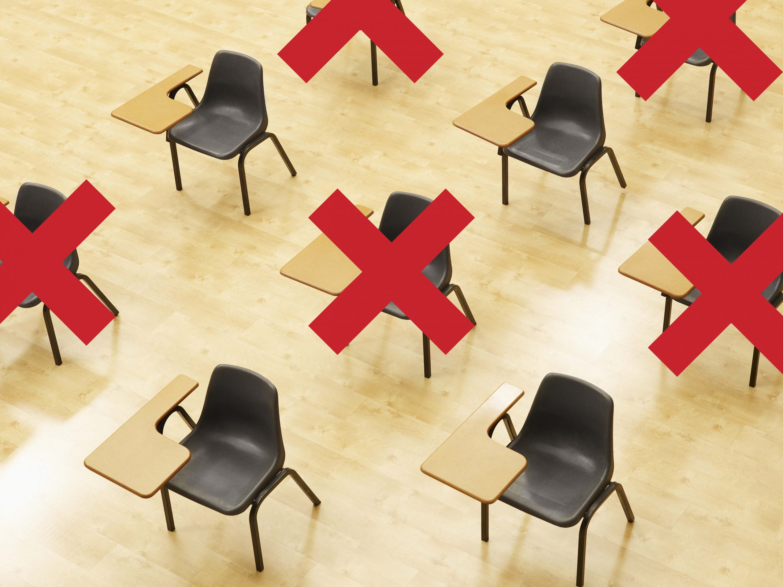 Desks in empty classroom with social distancing guidelines